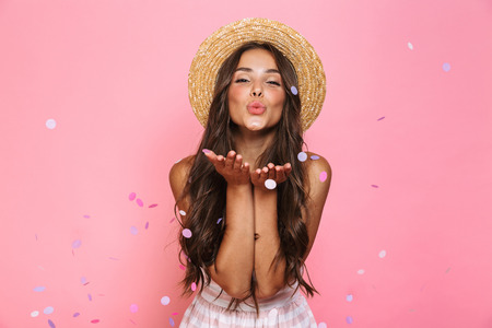 Photo of charming woman 20s wearing straw hat laughing while standing under confetti isolated over pink background Standard-Bild - 110904890