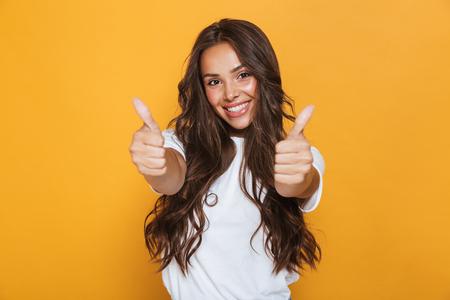 Imagen de mujer joven feliz aislada sobre fondo amarillo mostrando los pulgares para arriba gesto. Foto de archivo