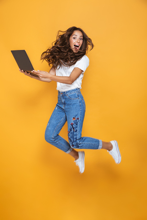 Full length portrait of a pretty girl with long dark hair jumping over yellow background, using laptop computer