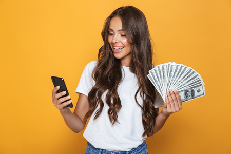Portrait of a happy young girl with long brunette hair standing over yellow background, holding money banknotes, using mobile phone Stok Fotoğraf