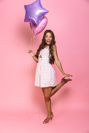 Full length portrait of stylish young lady 20s with long hair wearing dress smiling and holding balloon isolated over pink background