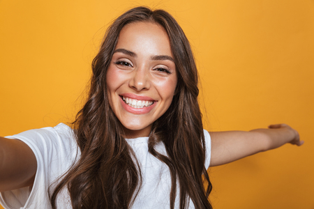 Portrait of caucasian woman 20s with long hair laughing while taking selfie photo isolated over yellow background Stockfoto