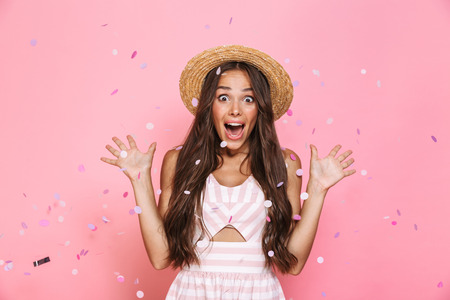 Photo of positive woman 20s wearing straw hat laughing while standing under confetti isolated over pink background Stock Photo