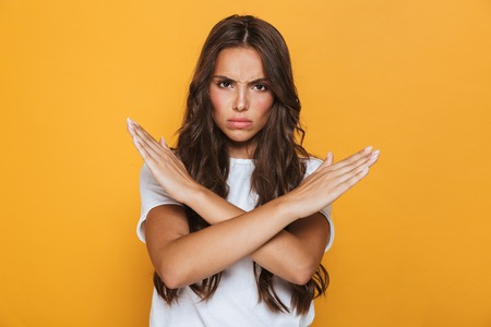 Portrait of a serious young girl with long brunette hair standing over yellow background, showing hands crossed gesture