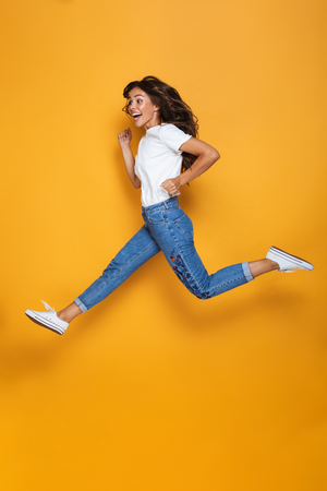 Full length portrait of a cheerful girl with long dark hair jumping over yellow background, looking away Banco de Imagens