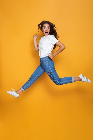 Full length portrait of a cheerful girl with long dark hair jumping over yellow background, looking at camera