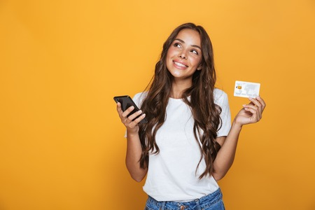 Portrait of a lovely young girl with long brunette hair standing over yellow background, holding mobile phone, showing plastic credit card