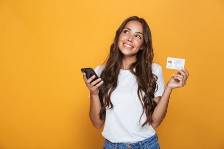 Retrato de una hermosa joven con cabello largo morena de pie sobre fondo amarillo, sosteniendo el teléfono móvil, mostrando una tarjeta de crédito de plástico