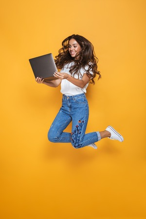 Full length portrait of a smiling girl with long dark hair jumping over yellow background, using laptop computer