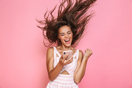 Photo of pretty woman 20s wearing dress smiling and holding smartphone with hair shaking isolated over pink background