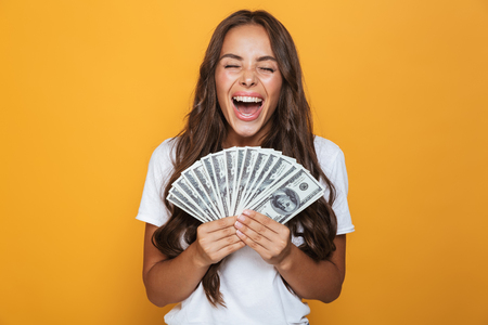 Portrait of a cheerful young girl with long brunette hair standing over yellow background, holding money banknotes 写真素材