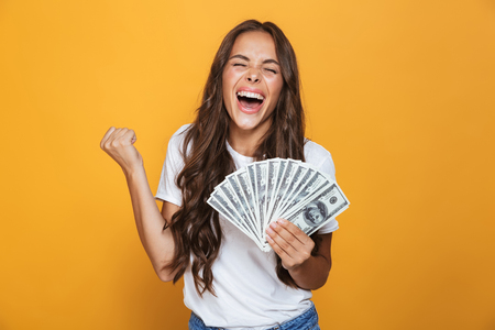 Portrait of a happy young girl with long brunette hair standing over yellow background, holding money banknotes, celebrating Foto de archivo