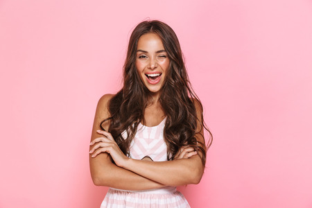 Image of cute woman 20s with long hair wearing dress smiling at camera with arms crossed isolated over pink background Stockfoto
