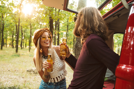 Photo of cheerful hippie couple man and woman smiling and drinking beer in forest near retro minivan