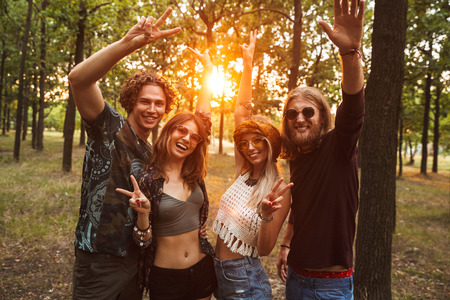 Photo of cheerful hippie people men and women smiling while walking in forest