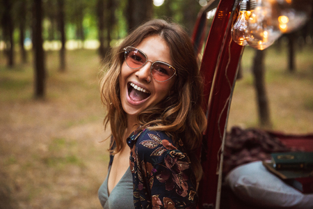 Image of excited woman 20s wearing stylish accessories smiling while resting in forest camp Stock Photo