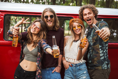 Group of happy hipsters men and women smiling and drinking beer near vintage minivan into the nature Stok Fotoğraf