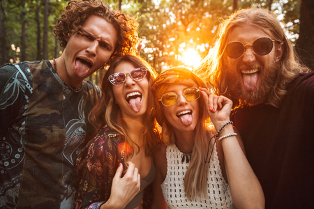 Photo of four hippie people men and women smiling and taking selfie in forest Stock Photo