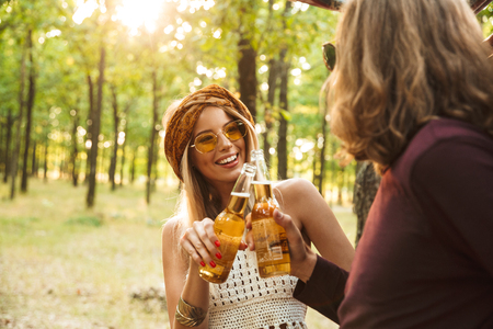 Photo of happy couple hipsters man and woman laughing and drinking beer in forest