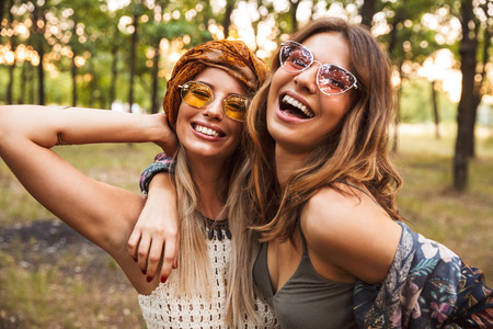 Photo of two young hippie girls smiling and hugging each other while walking in forest