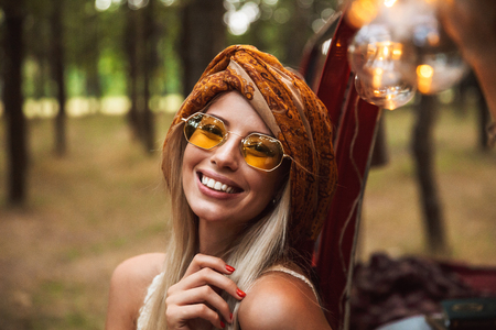 Photo of blond traveler woman wearing stylish accessories smiling while resting in forest camp