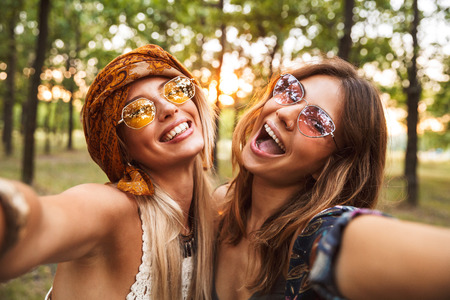 Photo of two joyful hippie women smiling and taking selfie while walking in forest
