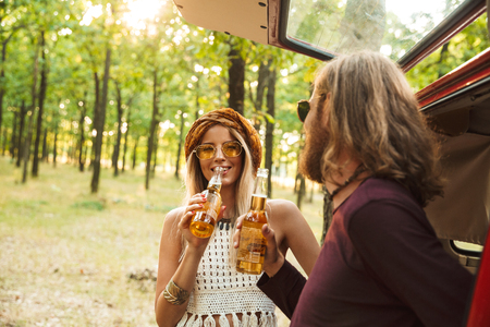 Photo of beautiful hippie couple man and woman smiling and drinking beer in forest near retro minivan Stock Photo