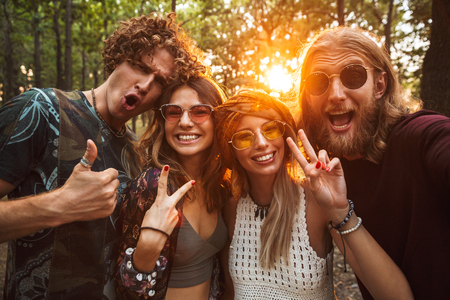 Photo of happy hippie people men and women smiling and taking selfie in forest