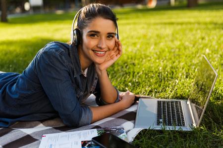 Bild der erstaunlichen schönen jungen Studentin im Park, die Musik des Laptop-Computers mit Kopfhörern hört. Standard-Bild