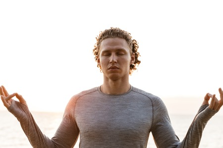 Handsome young sports man on the beach meditate outdoors. Stock Photo