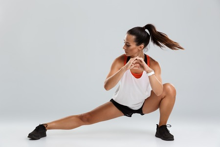 Image of strong beautiful young sports woman make stretching exercises isolated indoors. Stock Photo