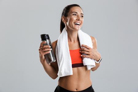 Bild einer schönen, stark lächelnden jungen Sportfrau, die isoliert drinnen Trinkwasser mit Handtuch am Hals posiert. Standard-Bild