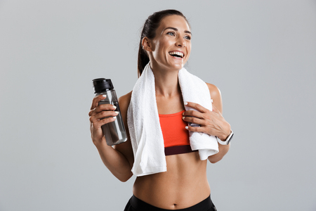 Image of a beautiful strong smiling young sports woman posing isolated indoors drinking water with towel on neck.