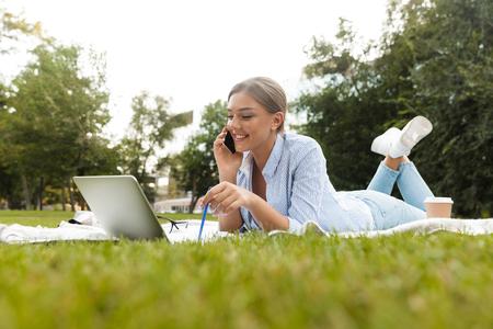Lächelndes junges Mädchen, das Zeit im Park verbringt, studiert, mit Laptop auf eine Decke legt, mit dem Handy spricht