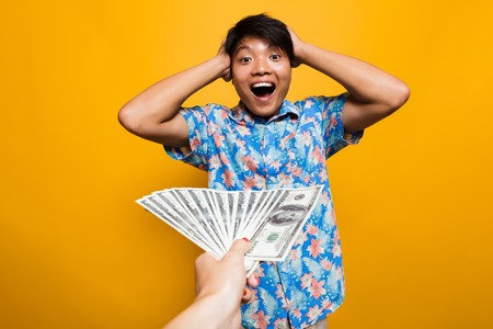Surprised happy asian man receiving money banknotes isolated over yellow background