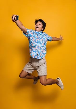 Bild des glücklichen emotionalen jungen asiatischen Mannes, der lokalisiert über gelbem Hintergrund springt, nehmen ein selfie durch Handy.