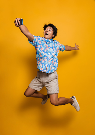Image of happy emotional young asian man jumping isolated over yellow background take a selfie by mobile phone.
