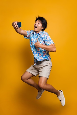 Image of happy emotional young asian man jumping isolated over yellow background take a selfie by mobile phone with thumbs up. Archivio Fotografico