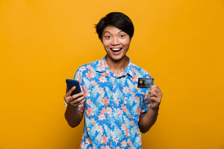 Image of a excited happy young asian man standing isolated over yellow background using mobile phone holding credit card. Standard-Bild