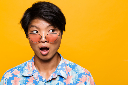 Close up portrait of a shocked asian man in sunglasses isolated over yellow background, looking away