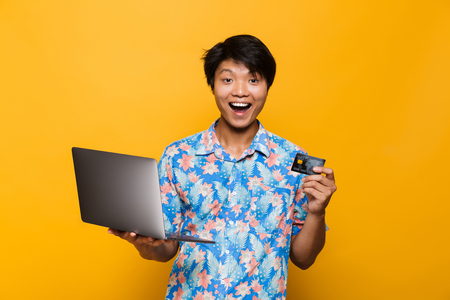 Portrait of an excited asian man isolated over yellow background, holding laptop computer, showing plastic credit card