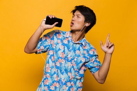 Image of emotional excited young asian man standing isolated over yellow background using mobile phone listening music with earphones singing.
