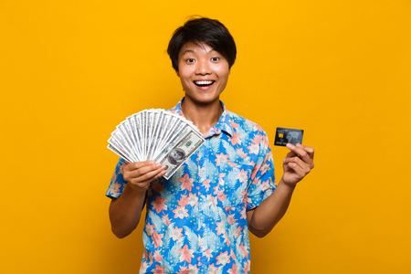 Image of happy young asian man standing isolated over yellow background holding money and credit card.