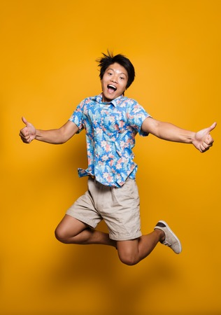 Image of happy emotional young asian man jumping isolated over yellow background showing thumbs up.