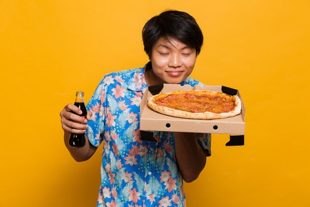 Image of pleased young asian man standing isolated over yellow background holding pizza smell drinking soda.