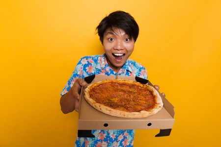 Image of excited happy young asian man standing isolated over yellow background holding pizza. Banco de Imagens - 111043053
