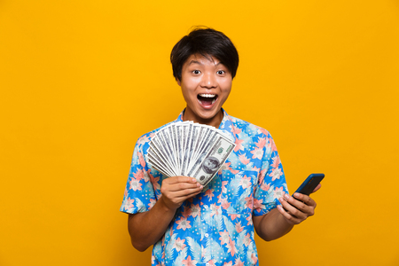 Image of happy young asian man standing isolated over yellow background holding money and using mobile phone.