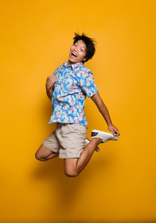 Image of happy emotional young asian man jumping isolated over yellow background. Stock fotó
