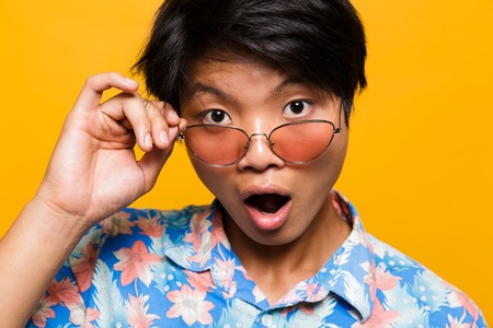 Close up portrait of a shocked asian man in sunglasses isolated over yellow background, looking at camera Foto de archivo