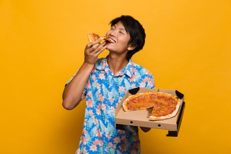 Image of happy young asian man standing isolated over yellow background eat pizza.